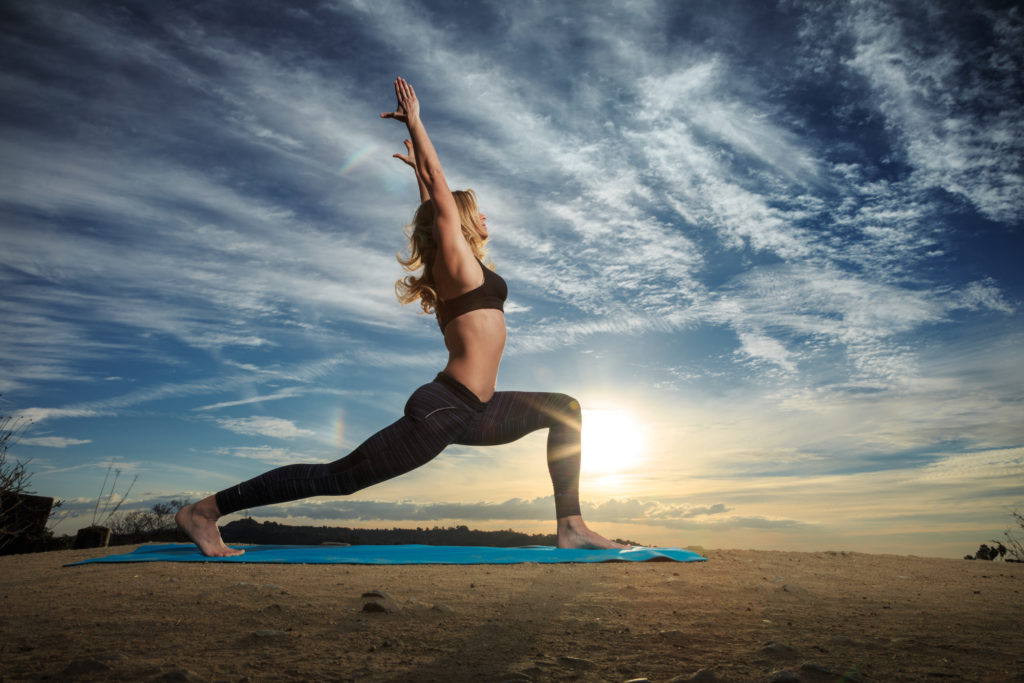 Resized Dancer in lunge on yoga mat on the sand shutterstock_174996662